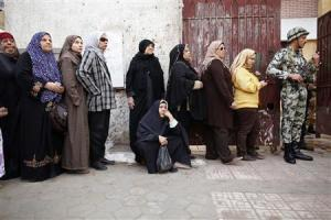 A elderly woman sits as she queues outside a polling center to vote during a referendum on Egypt's new constitution in Cairo